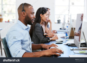 people sat working at computers in an office with headsets